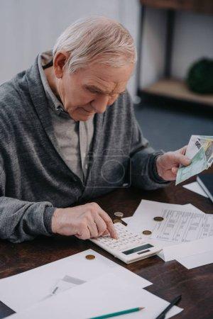 Photo pour Senior homme assis à table avec de la paperasse et en utilisant la calculatrice tout en comptant l'argent à la maison - image libre de droit
