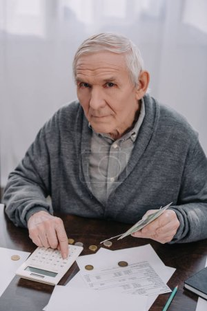 Photo pour Senior homme assis à table avec de la paperasse, en utilisant la calculatrice tout en comptant l'argent et regardant la caméra - image libre de droit