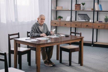 Senior sitzt mit Papierkram am Tisch und benutzt Taschenrechner, während er im Wohnzimmer Geld zählt