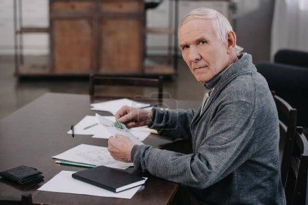 Photo pour Senior homme assis à table avec de la paperasse, regardant la caméra et tenant l'enveloppe avec l'argent - image libre de droit
