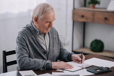Senior sitzt mit Papierkram am Tisch und schreibt in Notizbuch