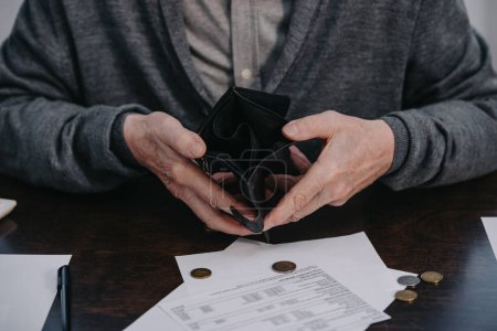Photo for Cropped view of male pensioner sitting at table with paperwork and holding empty wallet - Royalty Free Image