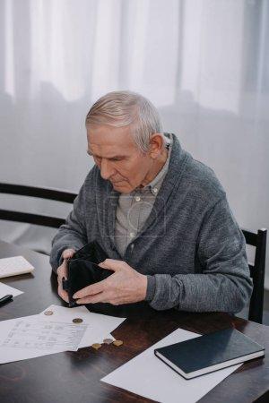 Photo pour Retraité assis à table avec de la paperasse et la tenue de portefeuille vide - image libre de droit