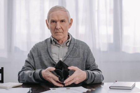 Photo pour Retraité assis à table avec de la paperasse, regardant la caméra et détenant le portefeuille vide - image libre de droit