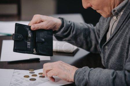 Photo pour Retraité assis à table avec de la paperasse et de compter l'argent - image libre de droit