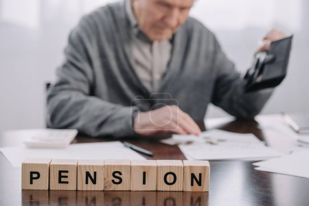 Photo for Selective focus of word 'pension' made of wooden blocks with male pensioner holding wallet on background - Royalty Free Image