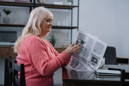 senior woman sitting at table and reading business newspaper at home