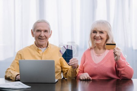 Photo pour Senior couple with air tickets, passports and credit card siiting at table with laptop and looking at camera - image libre de droit