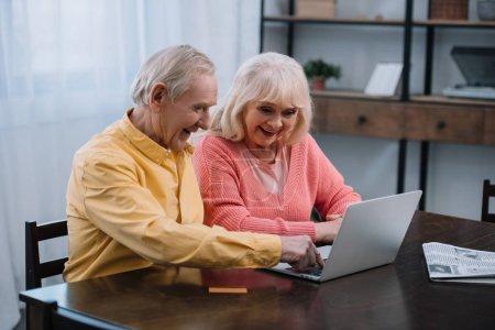 Photo pour Sourire couple aîné à l'aide d'un ordinateur portable tout en étant assis à la table à la maison - image libre de droit