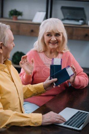 Photo pour Senior homme tenant des billets d'avion et passeports près surprise femme gesticulant avec les mains à la maison - image libre de droit