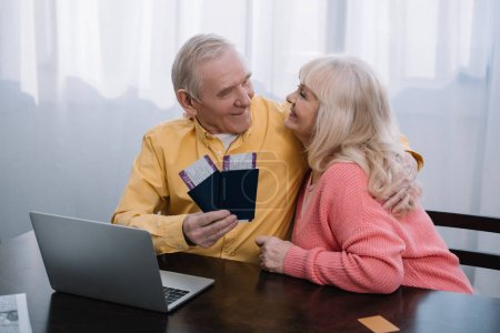 Photo for Smiling senior couple sitting at table with laptop, hugging and holding air tickets with passports at home - Royalty Free Image