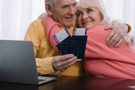 Photo pour Happy senior couple sitting at table with laptop, hugging and holding air tickets with passports at home - image libre de droit
