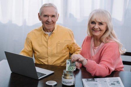 """Seniorenpaar sitzt mit Laptop am Tisch und blickt in die Kamera, während Frau Geld in Glas mit """"Rente"""" -Schriftzug steckt"""