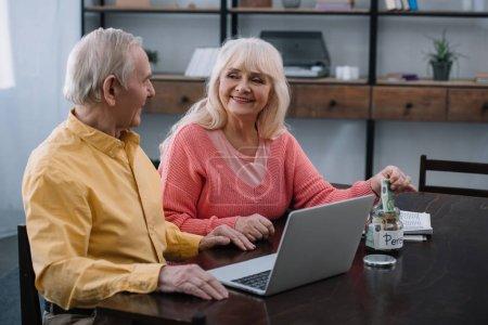 Photo pour Couple de personnes âgées assis à table avec ordinateur portable tandis que femme mettre de l'argent en pot de verre avec le lettrage «pension» - image libre de droit