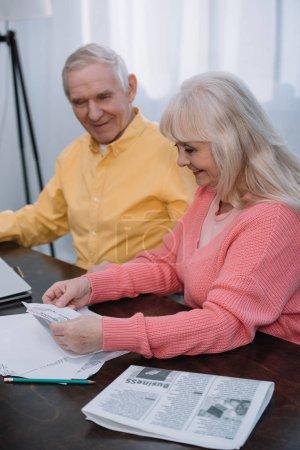 Lächelndes Seniorenpaar in bunten Kleidern sitzt mit Wirtschaftszeitung am Tisch