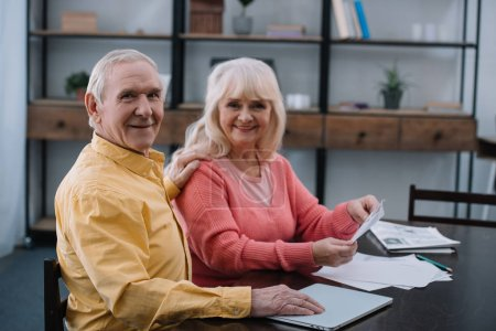Photo for Happy senior couple looking at camera while sitting at table with documents - Royalty Free Image