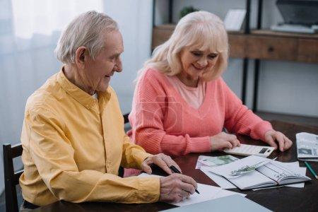 Photo pour Sourire supérieur coupé assis à table avec calculatrice et compter l'argent - image libre de droit