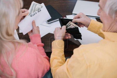 Photo pour Vue arrière du couple de personnes âgées tenant argent et enveloppe avec lettrage «roth ira» tout en étant assis à table - image libre de droit