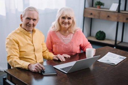 Lächelndes Seniorenpaar blickt in die Kamera und benutzt Laptop, während es zu Hause am Tisch sitzt