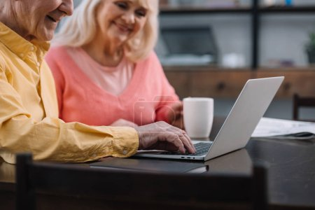 smiling senior couple in colorful clothes sitting at table and using laptop