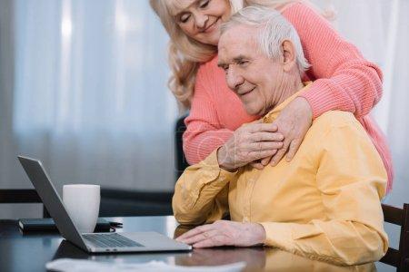 Photo pour Smiling couple de personnes âgées étreindre tandis que l'homme assis à table et à l'aide d'ordinateur portable - image libre de droit