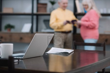 selective focus of laptop and newspaper on table with senior couple on background