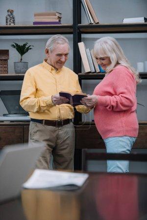 Seniorenpaar in bunten Kleidern liest Buch im Wohnzimmer