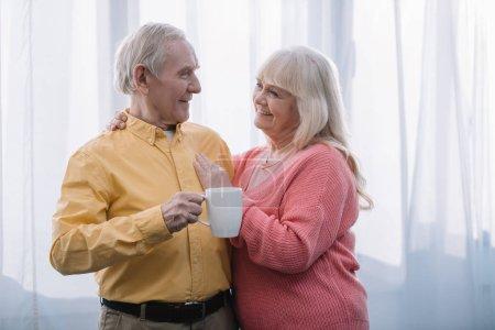 Lächelnde Seniorin mit grauen Haaren blickt in die Kamera und umarmt Mann mit Tasse Tee zu Hause