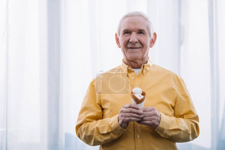 senior man looking at camera and holding ice cream cone at home with copy space