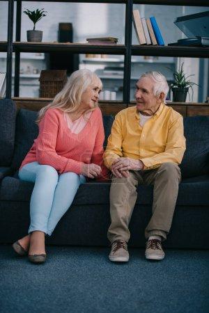 Seniorenpaar in legerer Kleidung sitzt auf Couch im Wohnzimmer