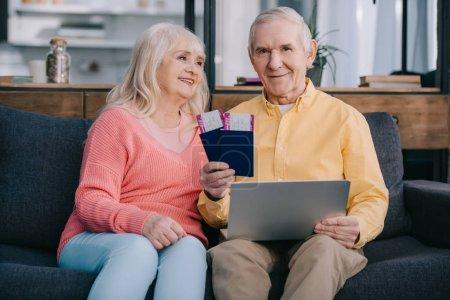 Photo pour Souriant couple de personnes âgées détenant des billets d'avion, portable et passeports en position assise sur canapé à la maison - image libre de droit