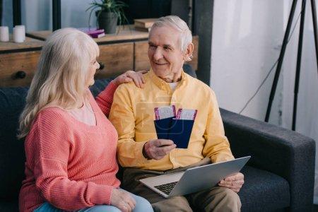 Photo pour Heureux couple senior détenant des billets d'avion avec des passeports en position assise sur le canapé à la maison - image libre de droit