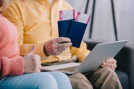 Photo pour Vue recadrée de couple de personnes âgées montrant le pouce en haut signe et détenant des billets d'avion avec des passeports - image libre de droit