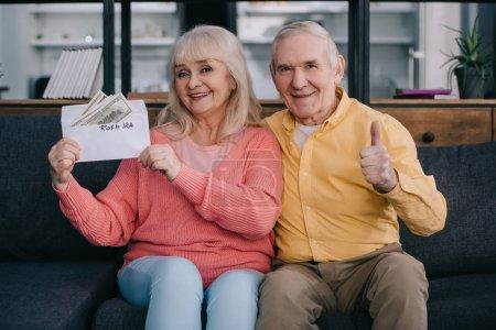 """Seniorenpaar zeigt Daumen hoch, während es einen Umschlag mit """"roth ira"""" -Schriftzug und Dollarnoten in der Hand hält"""