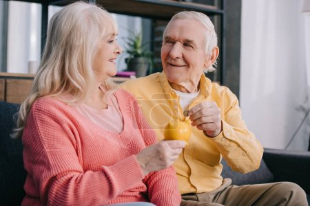 happy senior couple putting coin in yellow piggy bank
