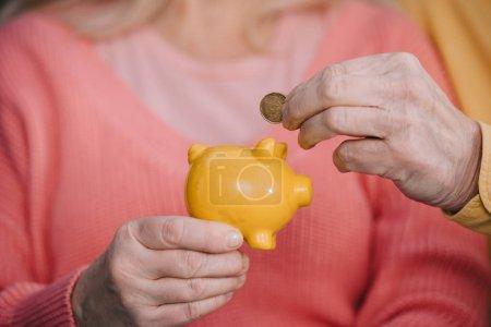 Photo pour Recadrée de l'homme senior mettant pièce dans la tirelire jaune - image libre de droit