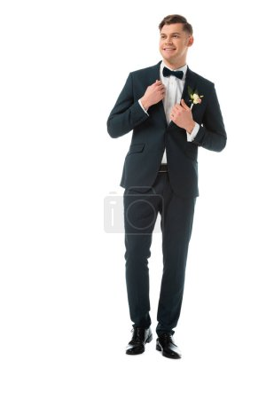 Photo for Happy bridegroom in elegant black suit with boutonniere isolated on white - Royalty Free Image