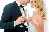 """Постер, картина, фотообои """"Счастливая невеста и жених звон бокалов шампанского, стоя лицом к лицу, изолированные на белом"""""""