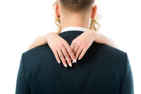 Photo pour Vue arrière du marié étreint par la mariée isolée sur blanc - image libre de droit