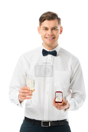 Photo for Happy groom holding glass of champagne and gift box with wedding ring isolated on white - Royalty Free Image