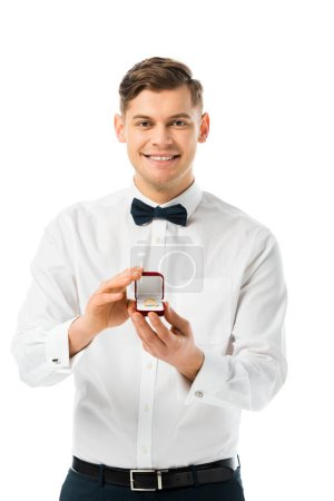 Photo for Happy groom demonstrating gift box with wedding ring and looking at camera isolated on white - Royalty Free Image