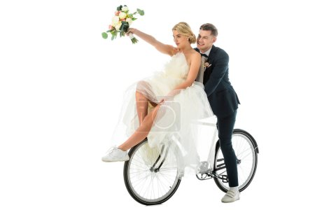 Photo for Beautiful bride holding wedding bouquet in raised hand while sitting on bicycle together with groom isolated on white - Royalty Free Image