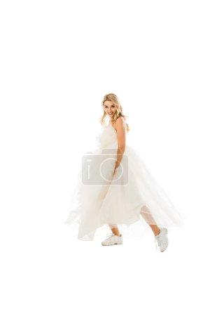 Photo pour Bel marié en robe de mariée et de baskets de danse tout en regardant la caméra isolé sur blanc - image libre de droit