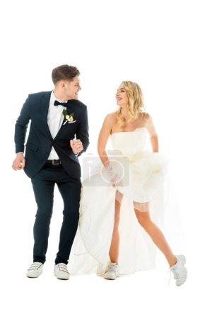 Photo pour Heureux époux et épouse, danser dans les vêtements élégants et des espadrilles en regardant l'autre isolé sur blanc - image libre de droit