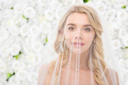 Photo pour Portrait de belle jeune mariée avec visage recouvert d'un voile nuptial transparent sur fond floral blanc - image libre de droit