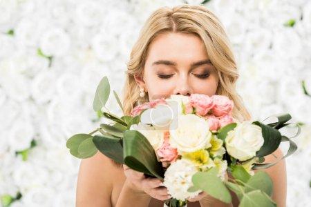 Photo pour Foyer sélectif de la jeune mariée avec les yeux fermés profiter de la saveur du bouquet de mariage sur fond floral blanc - image libre de droit