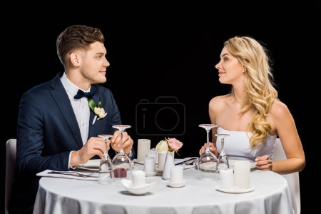 handsome groom and beautiful bride sitting at served table isolated on black