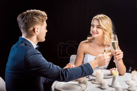 Photo for Happy couple clinking glasses of champagne while sitting at served table isolated on black - Royalty Free Image