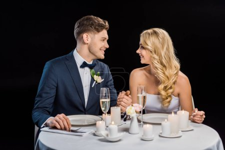 Photo for Happy young groom and bride holding hands while sitting at served table isolated on black - Royalty Free Image
