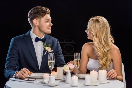 happy young couple sitting at served table and looking at each other isolated on black